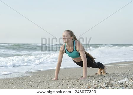 Girl In Sportswear Standing In A Bar On The Beach, Waves In The Background.