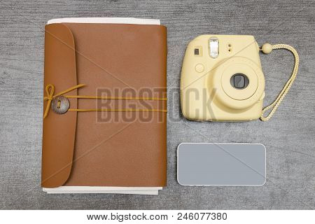 Yellow Camera, A Leather Notebook And Smartphone On A Black Table. Top View