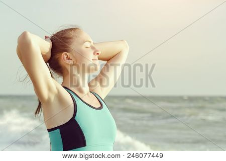 Girl On The Beach Standing With Eyes Closed And Hands Behind Head. Morning Sun