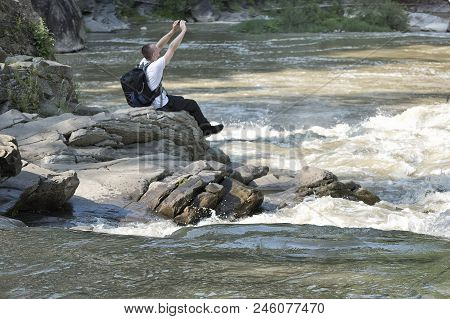 Young Man On The Bank Of A Stormy River Takes A Photo On A Smartphone. Sunny Summer Day