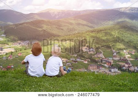 Two Boys Sitting On A Hill And Looking At The Mountains. Back View
