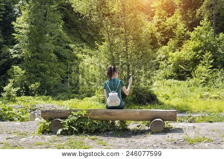 Girl With A Backpack Near The Forest Takes A Photo On A Smartphone. Back View. Summer Sunny Day