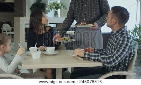 Young Family Take A Meal In Cafe Or Restaurant. Waiter