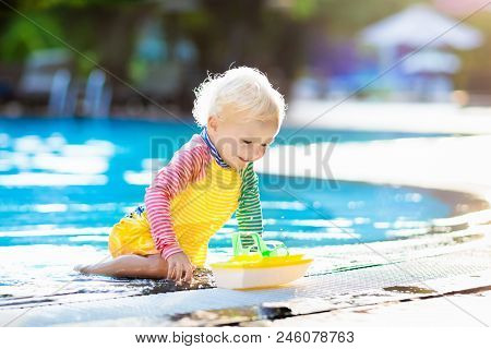 Baby In Swimming Pool. Family Summer Vacation.