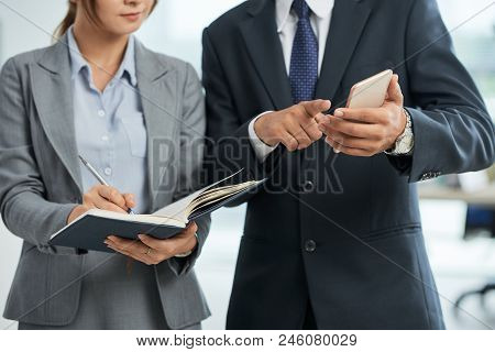 Businessman Showing His Daily Routine To His Secretary While She Making Notes In Notebook