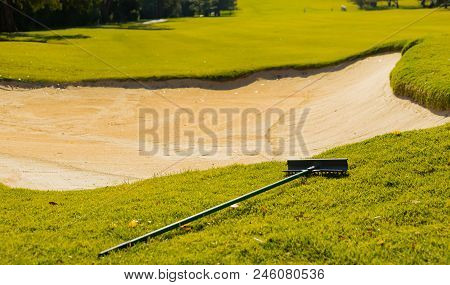 Sand Bunker Hazard and rake on Golf Course Fairway in afternoon light poster