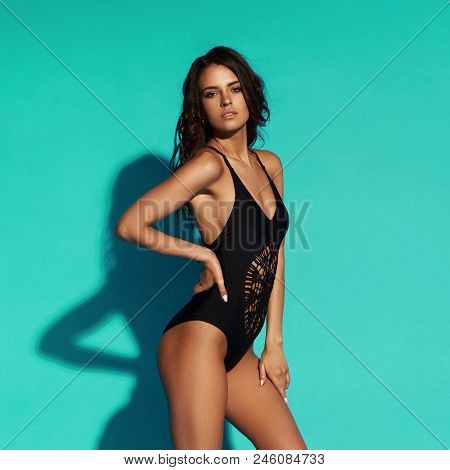 Young Sexy Slim Tanned Woman In Black Swimsuit Posing Against Blue Background. Full Length Fashion P