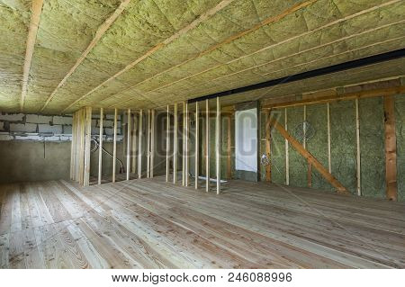 Construction and renovation of big spacious empty unfinished attic room with oak floor, walls and ceiling insulated with rock wool and fiber glass for cold barrier and wooden frame for future walls. poster