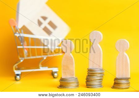 People Stand On Coins On The Background Of A Wooden House In Supermarket Trolley. Concept Of Real Es