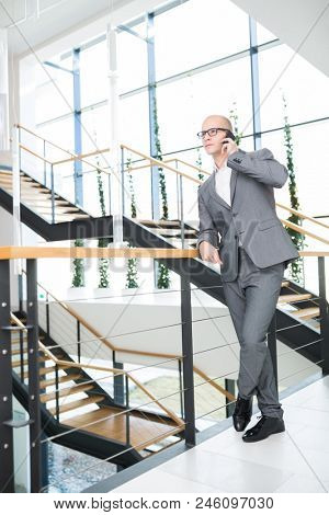 Full length of confident businessman using smartphone while leaning on railing in office