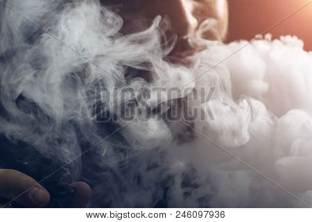 Man Vape E-cigarette With E-liquid, Close-up, Breathes Out Large Cloud Of Steam Or Vapor. Vaping Con