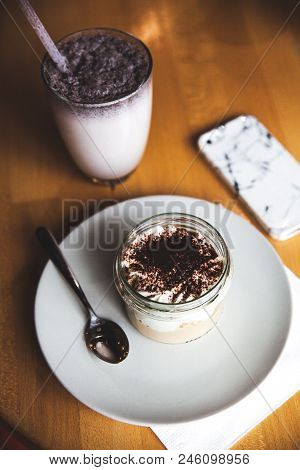 Milkshake In Plastic Cup On White Wooden Background A