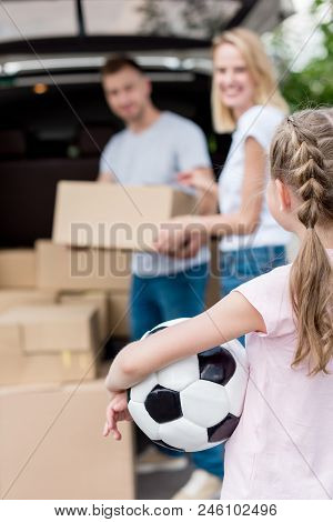Cropped Shot Of Little Child Holding Soccer Ball While Her Parents Unpacking Cardboard Boxes For Rel