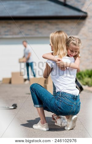 Back View Of Woman Hugging Smiling Daughter And Man Unpacking Cardboard Boxes Behind In Yard Of New
