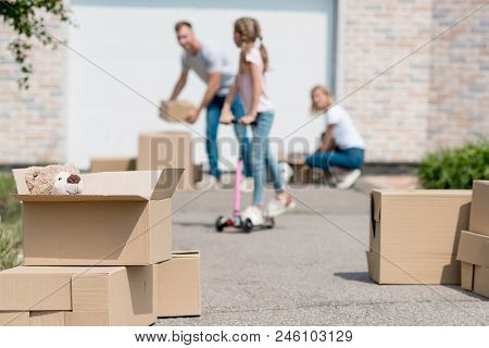 Close Up View Of Teddy Bear In Box And Couple Unpacking Cardboard Boxes Behind While Their Daughter