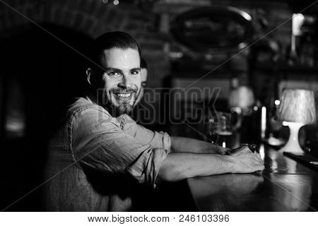 Man With Alcohol Near Bar Counter. Bearded Man With Happy Face Holds Glass Of Shot On Blurred Bar Ba