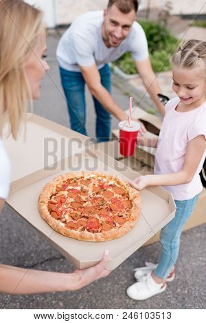 Mother Holding Box With Pizza And Daughter Taking Slice Of Pizza While Father Unpacking Cardboard Bo
