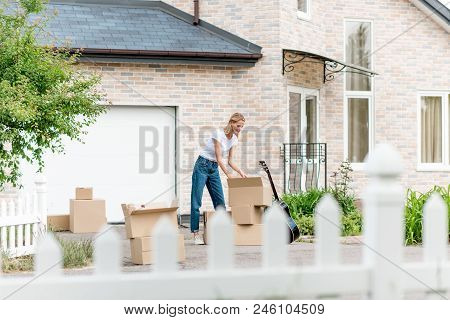 Woman Unpacking Cardboard Boxes Near Guitar In Front Of New House