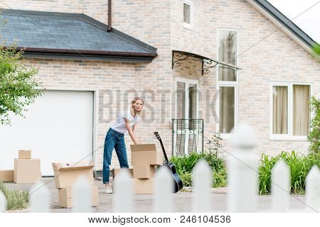 Distant View Of Young Woman Unpacking Cardboard Boxes Near Guitar In Front Of New House