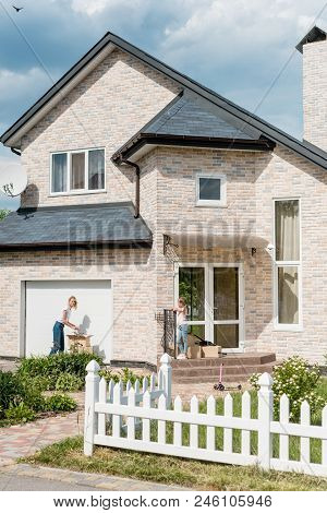 Distant View Of Woman Unpacking Cardboard Boxes While Daughter Standing On Stairs Of New Cottage