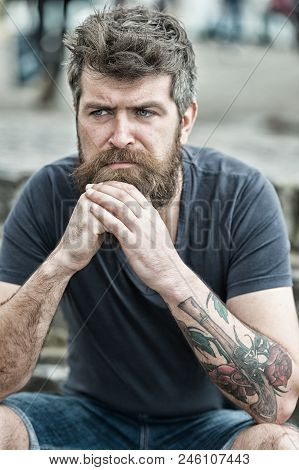 Man With Beard And Mustache Sits Outdoor. Bearded Man On Serious Face Looks Sad And Troubled, Suffer