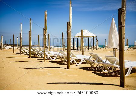 Algarve, Portugal, A Stunning Sea Ocean Landscape With Sunbeds And Umbrellas.  Cabo Da Roca, Portima