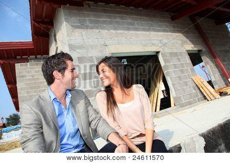 Pareja feliz sentado delante de la casa en construcción