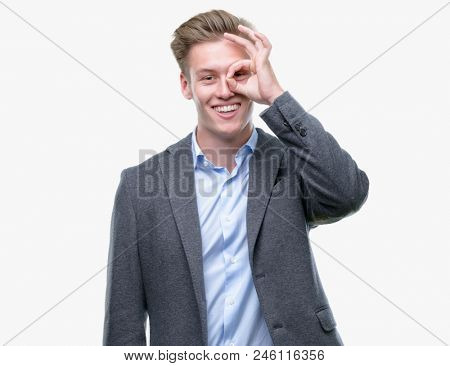 Young handsome blond business man doing ok gesture with hand smiling, eye looking through fingers with happy face.