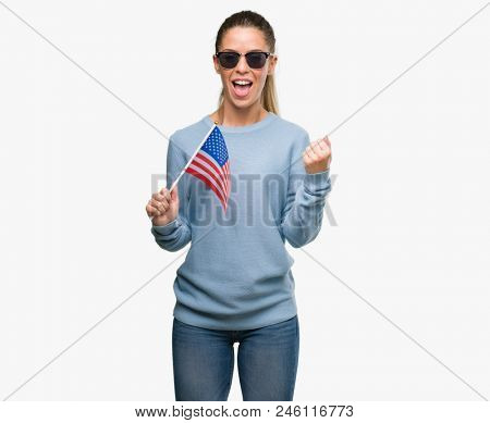 Beautiful young woman holding USA flag screaming proud and celebrating victory and success very excited, cheering emotion
