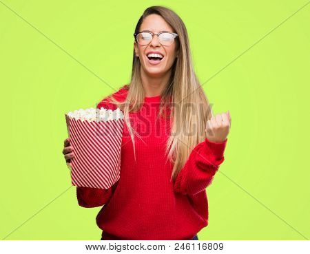 Beautiful young woman eating popcorn screaming proud and celebrating victory and success very excited, cheering emotion