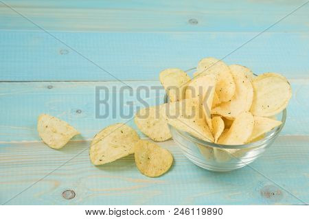 Potato Chips With Spicy In A Glass Bowl On A Blue Wooden Background. Concept Of Unhealthy Food. Salt