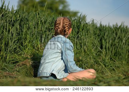 Alone Blond Hair Young Girl Sits On Path, On Her Back, Dressed In Jeans Blue Jacket And Shorts, Has