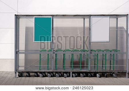 A Plastic Shelter With Trolley Outside In Front Of The Entrance Of A Beverage Dealer.