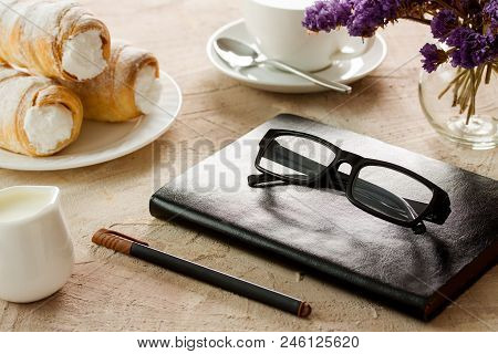 Black Leather Notepad, Black-rimmed Spectacles, Pen With Brown Cap, White Coffee Cup, Rolls With