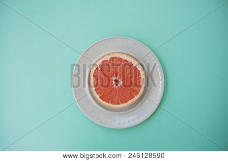 Ripe Juicy Cut Grapefruit On A White Plate On Blue Background With Text Space.