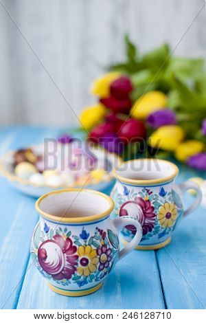 Easter Sweets For The Holiday. Spring. Bright Colors On Coffee Mugs. A Bouquet Of Fresh Tulips