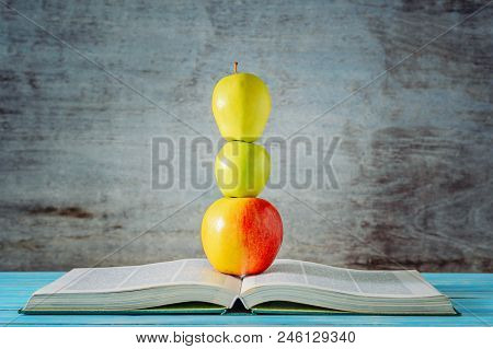 Open Book And Three Apples Stacked In Front Of Wooden Background