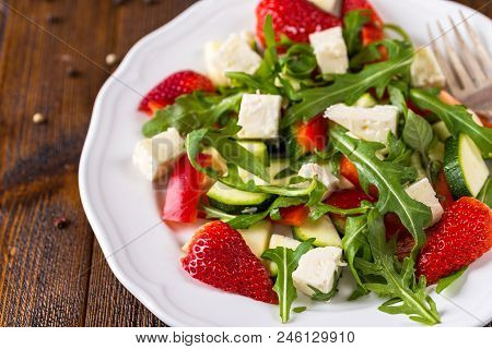 Fresh Vegetable Strawberry Salad On White Plate On Natural Rustic Desk.