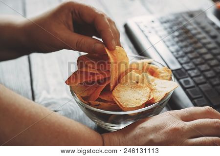 Unhealthy Snack At Workplace. Hands Of Woman Working At Computer And Taking Chips From The Bowl. Bad