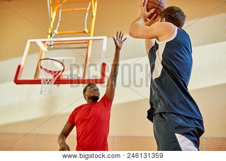African-american Man Trying To Stop Contender From Throwing Ball Into Basket While Playing Basketbal