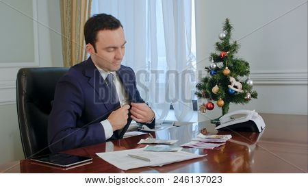Happy Young Businessman Counts Salary Near New Year Tree In
