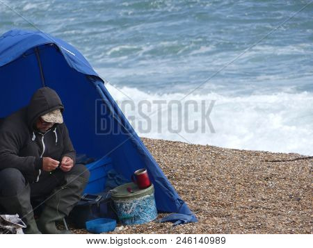 Weymouth, England - June 20 2018: Male Fisherman Rolling A Cigarette In His Shelter At Chesil Beach,