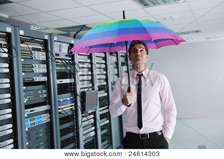 young handsome business man  engineer in  businessman hold  rainbow colored umbrella in server datacenter room  and representing security and antivirus sofware protection concept poster