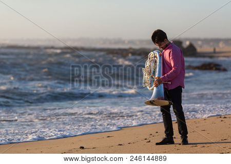 Musician with Tuba on the ocean coast.