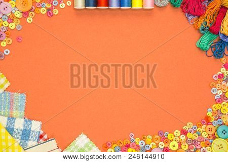 Arts and Crafts background with material and buttons on an orange textured paper background with blank copy space.