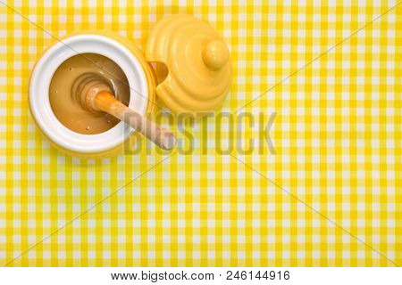 A beehive themed pot full of Manuka honey with wooden dipper on a yellow gingham background with copy space.