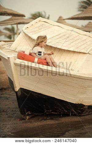 Young Navigator. Small Kid Sit On Wooden Boat At Beach. Childhood And Baby Care Concept. Marine Safe