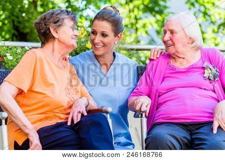 Geriatric nurse having chat with senior women in retirement home