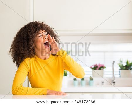African american woman wearing yellow sweater at kitchen shouting and screaming loud to side with hand on mouth. Communication concept.