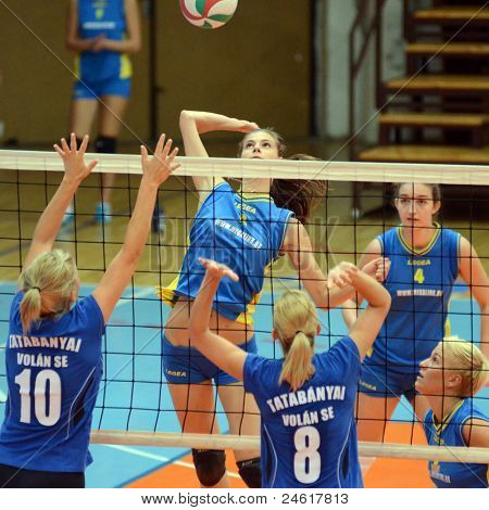 KAPOSVAR, HUNGARY - OCTOBER 2: Zsofia Harmath (in the top) in action at a Hungarian NB I. volleyball game Kaposvar (yellow number) vs Tatabanya (white number), October 2, 2011 in Kaposvar, Hungary.